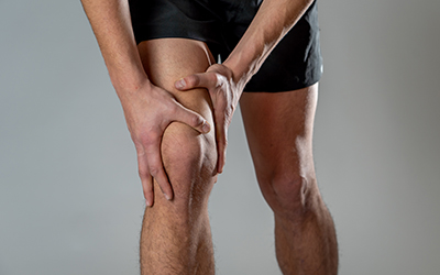 Sport man injured when exercising or running holding his knee in