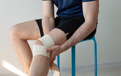 Sporty young man bandaging his knee. Pain in knees. Knee sprain