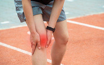 Close up of runner woman holding her knee, sufferring from Knee