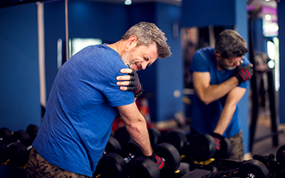 Man feeling strong shoulder pain while training with dumbbells i