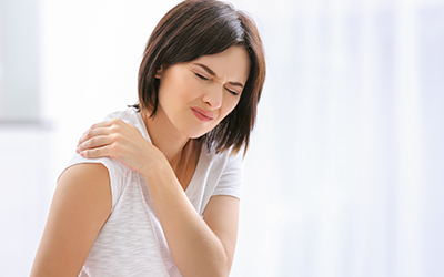 Beautiful young woman suffering from pain in shoulder at home