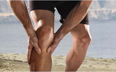 young sport man with athletic legs holding knee in pain sufferin