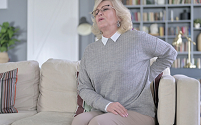 Exhausted Old Woman having Back Pain while Sitting on Sofa