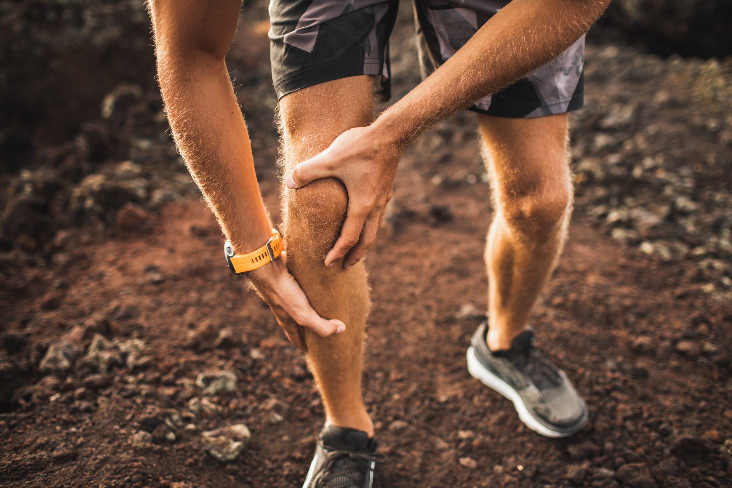 Knee injury on running outdoors. Man holding knee by hands close